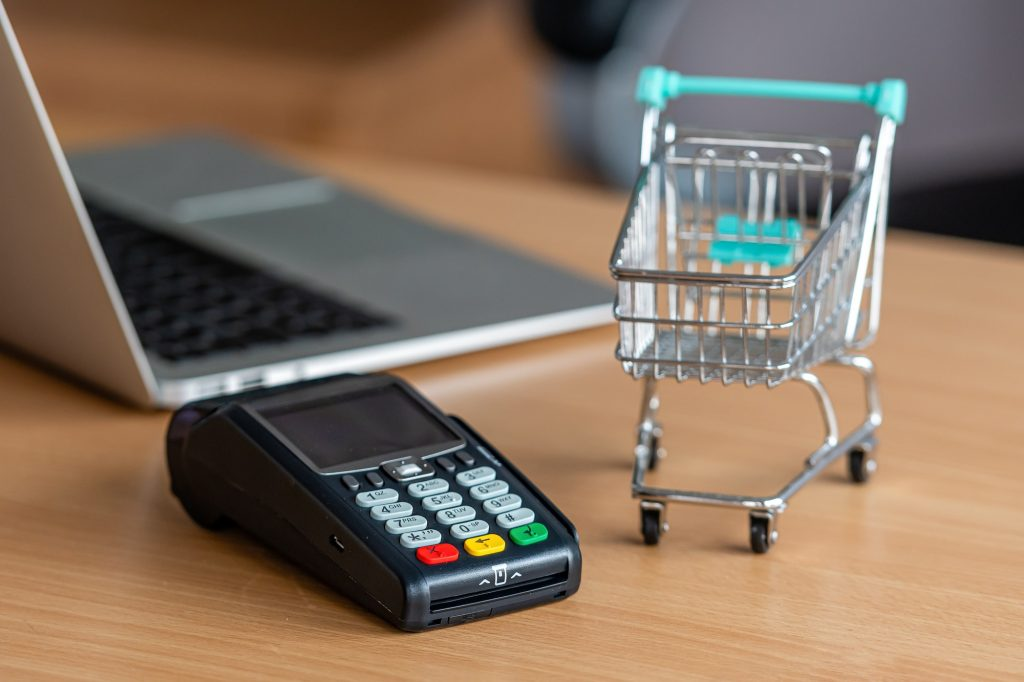 credit card terminal on table in the store with credit card, laptop and mini shopping cart on table